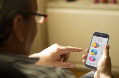 Retrato de un hombre maduro con las finanzas app en un teléfono móvil Imagen de archivo libre de regalías