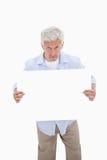 Retrato de un hombre maduro que lleva a cabo a una tarjeta en blanco Fotos de archivo libres de regalías