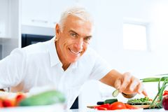 Retrato de un hombre mayor elegante que cocina en cocina foto de archivo
