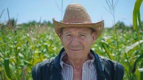 Retrato de un hombre mayor en un sombrero de paja contra la perspectiva de un campo de maíz Un granjero en su tierra rodeada cerc almacen de video