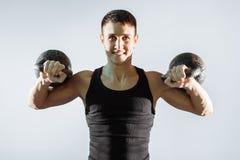 Retrato de un hombre muscular sonriente que realiza ejercicios con los pesos Foto de archivo libre de regalías