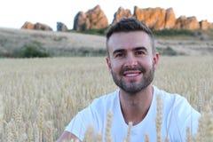 Retrato de un hombre natural magnífico joven que se sienta en un campo de trigo Foto de archivo