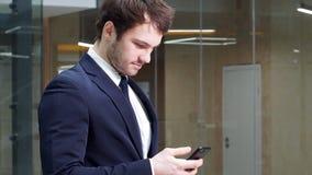 Retrato de un hombre de negocios acertado joven que usa un smartphone en oficina moderna metrajes