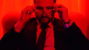 Retrato de un hombre de negocios barbudo acertado vestido en un traje de negocios que pone en los vidrios que se sientan en luz r almacen de metraje de vídeo