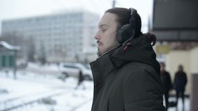 Retrato de un hombre de pelo largo joven con una barba en los auriculares que se colocan en una parada de la tranvía en invierno  almacen de video
