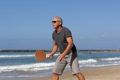 Retrato de un hombre que juega a tenis de la playa fotos de archivo