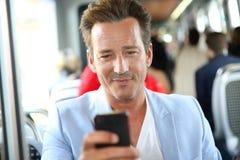 Retrato de un hombre que toma el tranvía usando smartphone Imagenes de archivo