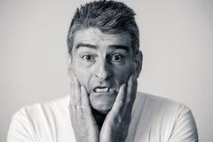 Retrato de un hombre de 40s 50s en choque con una expresión asustada en su cara que hace gestos asustados en sensaciones humanas  imagen de archivo