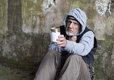 Retrato de un hombre sin hogar maduro que se sienta al aire libre sosteniendo hacia fuera una lata Fotografía de archivo libre de regalías
