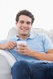 Retrato de un hombre sonriente que sostiene una taza de café Foto de archivo libre de regalías