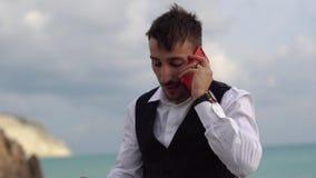 Retrato de un hombre trastornado, frustrado que habla en un tel?fono m?vil cerca del mar con una visi?n imponente Hombre de negoc almacen de video