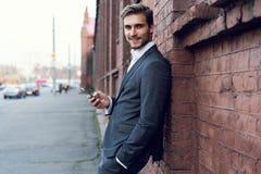 Retrato de un hombre vestido formal joven feliz que se inclina en una pared al aire libre que sostiene el teléfono móvil fotos de archivo libres de regalías