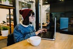 Retrato de un inconformista de la muchacha que utiliza un ordenador portátil en un café Fotografía de archivo