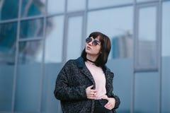 Retrato de un inconformista joven, hermoso, elegante de la muchacha que ajusta sus vidrios y la presentación en fondo urbano Foto de archivo libre de regalías