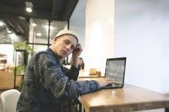 Retrato de un inconformista joven que trabaja para un ordenador portátil en un café acogedor y mira la cámara Freelancer en el tr Fotos de archivo