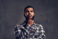 Retrato de un individuo afroamericano pensativo con una barba que lleva una camisa a cuadros fotos de archivo
