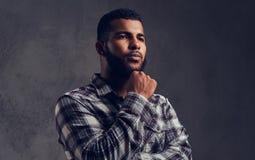 Retrato de un individuo afroamericano pensativo con una barba que lleva una camisa a cuadros fotografía de archivo libre de regalías