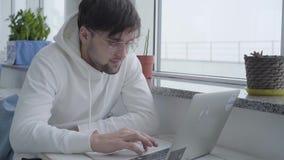 Retrato de un individuo barbudo hermoso elegante joven en una camiseta ligera y de mecanografiar en un ordenador portátil mientra almacen de video