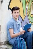 Retrato de un individuo del adolescente con una tableta en la calle Imagenes de archivo