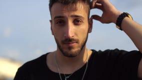 Retrato de un individuo joven que fija su pelo con su cierre de la mano para arriba Pelo oscuro grueso del tacto unshaved hermoso metrajes