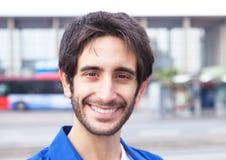 Retrato de un individuo latino de risa en una camisa azul en la ciudad Imagenes de archivo