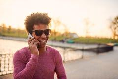 Retrato de un individuo sonriente que usa el teléfono móvil Imagen de archivo