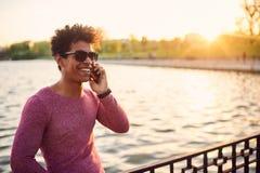 Retrato de un individuo sonriente que usa el teléfono móvil Fotos de archivo libres de regalías