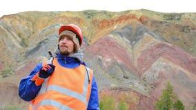 Retrato de un ingeniero de minas, de un geólogo en el chaleco reflexivo protector, de guantes y del casco, con el martillo a disp almacen de metraje de vídeo