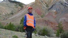Retrato de un ingeniero de minas, de un geólogo en el chaleco reflexivo protector, de guantes y del casco, con el martillo a disp metrajes