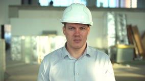 Retrato de un ingeniero de sexo masculino en casco A cámara lenta capataz con las armas dobladas en el inspección in situ del edi almacen de video