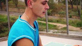 Retrato de un jugador de básquet de mirada serio joven que hace girar un baloncesto en el terreno de juego de la calle Tiro a cám almacen de metraje de vídeo