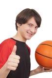 Retrato de un jugador de básquet sonriente hermoso que muestra el pulgar u Imagen de archivo