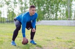 Retrato de un jugador de fútbol americano joven con una bola en el estante imagen de archivo