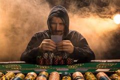 Retrato de un jugador de póker profesional que se sienta en la tabla del póker Foto de archivo