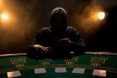 Retrato de un jugador de póker profesional que se sienta en la tabla del póker Imagenes de archivo