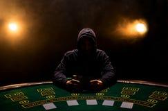 Retrato de un jugador de póker profesional que se sienta en la tabla del póker Foto de archivo libre de regalías