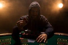 Retrato de un jugador de póker profesional que se sienta en la tabla del póker Imágenes de archivo libres de regalías