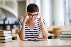 Retrato de un libro de lectura sonriente bonito de la muchacha en biblioteca Fotos de archivo