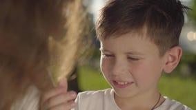 Retrato de un más viejo tiempo del gasto de la hermana con el hermano menor al aire libre El muchacho que toca el pelo de la much almacen de video
