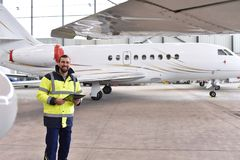 Retrato de un mecánico de aviones en un hangar con los jets en el ai foto de archivo