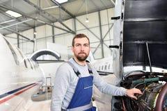 Retrato de un mecánico de aviones en un hangar con los jets en el ai imágenes de archivo libres de regalías