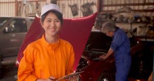 Retrato de un mecánico de coche hermoso joven en un taller del coche almacen de video