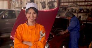 Retrato de un mecánico de coche hermoso joven en un taller del coche almacen de metraje de vídeo