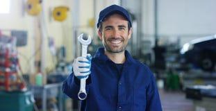 Retrato de un mecánico de coche hermoso joven en un taller de reparaciones del coche, manos con una llave inglesa Concepto: repar Imagen de archivo libre de regalías