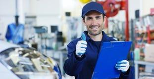 Retrato de un mecánico de coche hermoso joven en un taller del coche, en el fondo de una reparación del concepto del servicio del Fotos de archivo libres de regalías