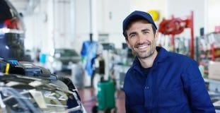 Retrato de un mecánico de coche hermoso joven en un taller del coche, en el fondo de una reparación del concepto del servicio del Foto de archivo