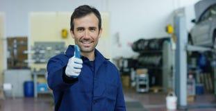 Retrato de un mecánico de coche hermoso joven en un taller del coche, en el fondo del servicio Concepto: reparación de máquinas,  Fotos de archivo