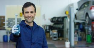Retrato de un mecánico de coche hermoso joven en un taller del coche, en el fondo del servicio Concepto: reparación de máquinas,  Imagen de archivo libre de regalías