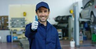 Retrato de un mecánico de coche hermoso joven en un taller del coche, en el fondo del servicio Concepto: reparación de máquinas,  Fotografía de archivo libre de regalías