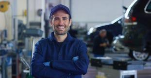 Retrato de un mecánico de coche hermoso joven en un taller del coche, en el fondo del servicio Concepto: reparación de máquinas,  Foto de archivo libre de regalías